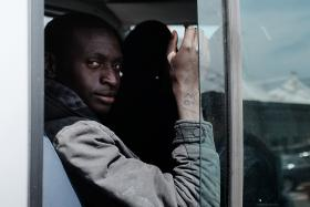 A rescued migrant with a number on his right arm, sits on bus after disembarking  at the Sicilian harbour of Catania on Thursday