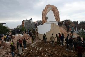 Nepalese rescue members and onlookers gather at the collapsed Darahara Tower in Kathmandu on April 25, 2015. A powerful 7.9 magnitude earthquake struck Nepal, causing massive damage in the capital with strong tremors felt across neighbouring countries.