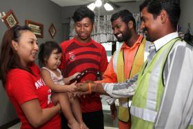 HEROES: Mr P. Muthukumar (in orange shirt) and Mr S. Shanmuganathan greeting Naureh Fitria Auni, the girl they saved, and her parents Madam Noreen Saniri and Mr Muhammad Fazlee Abdul Aziz.