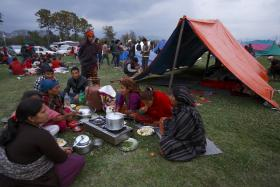 Family members eat their dinner in front of a makeshift shelter on open ground to keep safe after an earthquake in Kathmandu, Nepal .