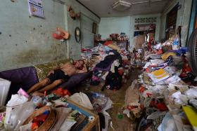 FILTHY: Mr Lim Chin Ting has to sleep on the sofa in the living room because both bedrooms are filled to the brim with rubbish.