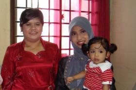 NEXT-DOOR BFFS: Madam Khaironisha Abdul Rahman (left) with her neighbour, Ms Jamalia Sukar, who is carrying her daughter.