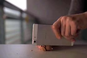 SMASH: Screengrabs from Youtube showing the durability of the Oppo R5 which manages to smash a watermelon and crack a nut.