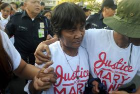 Celia Veloso (centre), the mother of Mary Jane Veloso is escorted by a supporter in Manila upon her return from Jakarta on Friday