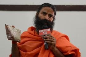 Baba Ramdev poses with an ayurvedic health product during a press conference in New Delhi on Friday