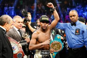 Floyd Mayweather Jr. celebrates the unanimous decision victory during the welterweight unification championship bout. They were celebrities galore at the match touted as the biggest this century.