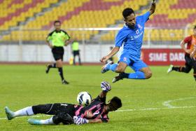 TOUGH GUYS: LionsXII's Nazrul Nazari (above) is foiled by Sime Darby goalkeeper Kamarul Effandi but the depleted Singaporean side collected all three points through Gabriel Quak's winner.
