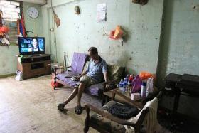 CLEARED: Mr Lim Chin Ting sitting comfortably in his cleared living room (above) for the first time in years.
