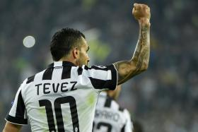 Juventus' forward from Argentina Carlos Tevez celebrates after scoring a penalty during the UEFA Champions League semi-final first leg football match.
