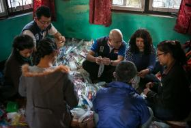 REACHING OUT: (Above) Mr Michael Tay (centre, in blue) and his team packing relief supplies in Nepal's Bagmati Zone.