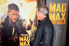 Isn't that supposed to be me? Mel Gibson stares at a poster of actor Tom Hardy at the Mad Max: Road Fury Premiere.