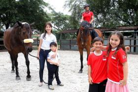 MUMS AND BABES: Soh Wei Chi (in white) with her son Kristian and horse Mirabel Horjis, and 1995 SEA Games gold-medallist Catherine Oh (in red) with her horse Vlicka and children Kai and Ella.