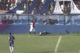 A screen capture of player Emanuel Ortega (lying down on the ground) right after he hit his head on the low wall which surrounds the pitch.
