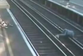 The man loses his footing while trying to cross the railway track.
