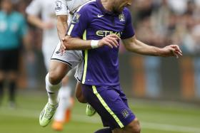 Swansea's Jefferson Montero (in white)  battling it out with Manchester City's Pablo Zabaleta