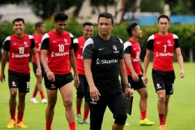 ON A MISSION: LionsXII coach Fandi Ahmad (in black) is focused as he puts his charges through training at the Geylang Field yesterday.