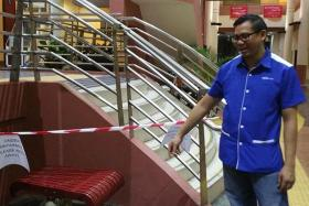 SCENE: A cleaner at Jurong Spring Community Club pointing to the spot where a woman got stuck.