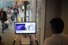 Passengers arriving from Doha, Qatar walking past a thermal scanner in Changi Airport on May 18 last year.