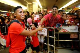 SIGN, SAHIL: Sahil Suhaimi shaking hands with a fan (above) and signing an autograph on the wraparound cover of yesterday's The New Paper after arriving at Changi Airport yesterday.