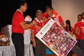 ALL THE BEST: National sprinter Calvin Kang receiving a poster and mascot from chefs de mission for the SEA Games Nicholas Fang (left) and Tan Eng Liang (centre).