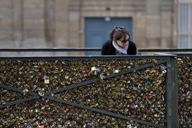 A woman looks at padlocks hanging on the Pont des Arts.