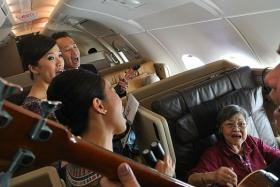 IN-FLIGHT ENTERTAINMENT: (Above, seated) Madam Esther Wee singing along on the flight.