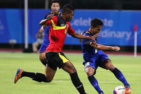 TWISTING TIME: Thailand's star Chanathip Songkrasin (in blue) turning away as Timor Leste's Frangcyatma Alves closes in.