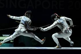 Singapore's Wang Wenying (right) duels with Justine Gail Tinio of the Philippines during the women's individual foil final at the 28th SEA Games.