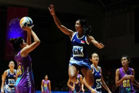 Singapore defender Premila Hirubalan tries to stop Thailand's Boonkong Yada from scoring during the netball semi-finals of the 28th SEA Games.