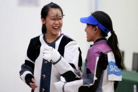 Tessa Neo celebrates with teammate Jasmine Ser after winning the women's 10m air rifle individual event of the 28th SEA Games.
