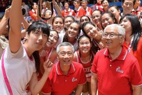 GOLDEN TIME: The victorious netball girls taking a wefie with Prime Minister Lee Hsien Loong (centre) and President Tony Tan Keng Yam (right).