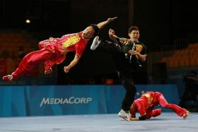 TEAMWORK: Singapore's wushu exponents in action in the men's duel barehand final yesterday.