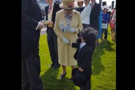 Mohammed Ahmed Jaber Al Harbi shakes the hand of Queen Elizabeth II at the Epsom Derby in Dubai.
