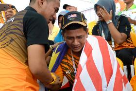SAME RESULT, DIFFERING EMOTIONS: Malaysia Muhd Hafizuddin Mat Daud (above) in tears after winning gold.