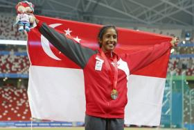 Shanti Pereira celebrates at the National Stadium after winning the women's 100m bronze at the 28th SEA Games.