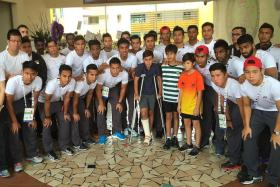 GIVING SUPPORT: The Singapore SEA Games football team during their visit to Tanjong Katong Primary School yesterday afternoon to pay respects to the victims of the Sabah earthquake. With them are Jayden Francis (in crutches), 12, Chaityak Khatwani (in stripes), 12, and Tristan So Kwan Wing (in orange), 12. Jayden was one of the pupils who went on the trip to Sabah with the school.