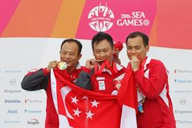 Singapore shooters Gai Bin, Lim Swee Hon and Poh Lip Meng celebrate their gold medal win in the men's 50m pistol team event of the 28th SEA Games.