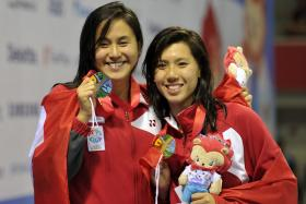 Amanda Lim (right) and Quah Ting Wen celebrate after receiving their gold and silver medals for the 50m freestyle race.