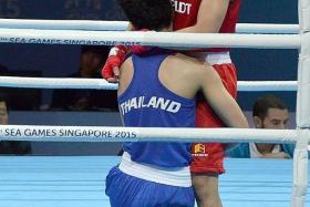 CLOSE FIGHT: Josie Gabuco (in red) beat 2014 World Championships light-flyweight bronze medallist Chuthamat Raksat in the SEA Games final yesterday.