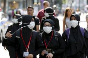 Tourists wearing masks to prevent contracting Middle East Respiratory Syndrome (MERS) walk at Myeongdong shopping district in central Seoul.