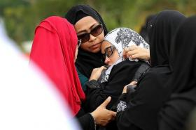 DISTRAUGHT: Ashmi Roslan's actress-host girlfriend Syirah Jusni (with white headscarf) had to be propped up by her friends during the burial.