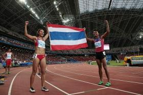 THAI DELIGHT: Thailand's Jamras Rittidet (right) and Wallapa Punsoongneun (left) celebrate winning the men's 110m hurdles and women's 100m hurdles respectively.
