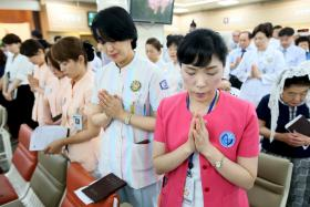 Hospital workers praying during a mass for Mers patients at a hospital in Seoul on Friday (June 12)