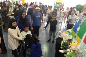 SAYING GOODBYE: Emyr Uzayr (with bandage) and El Wafeeq El Jauzy (in wheelchair) at the Tribute Corner at Tanjong Katong Primary School with their families.