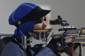 DRESSED FOR SUCCESS: Nur Ayuni Farhana (above) shooting her way to the gold medal.