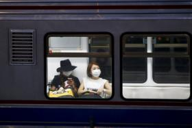 Women wearing masks to prevent contracting MERS ride subway train in Seoul.