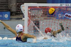 Thailand's Yuwadee Seenoon (No. 9) attacks Singapore's goal during the women's water polo finals.