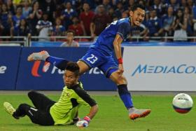 Thailand's Pombubpha Chananan (in blue) skips past Myanmar goalkeeper Kyaw Zin Phyo to score.