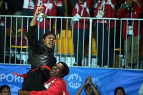 WHAT A RELIEF: Alfian gets a lift from Sheik Alau'ddin after beating Vietnam's world champion Tran Dinh Nam to claim silat's only gold at the Games.