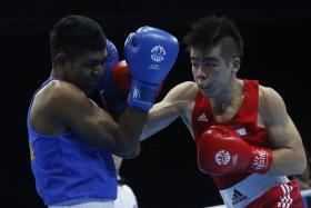 BRONZE MEDALLIST: Timor Leste's Henrique Martins Borges Pereira (left) being beaten by Singapore's Tay Jia Wei in the men's welterweight semi-finals.